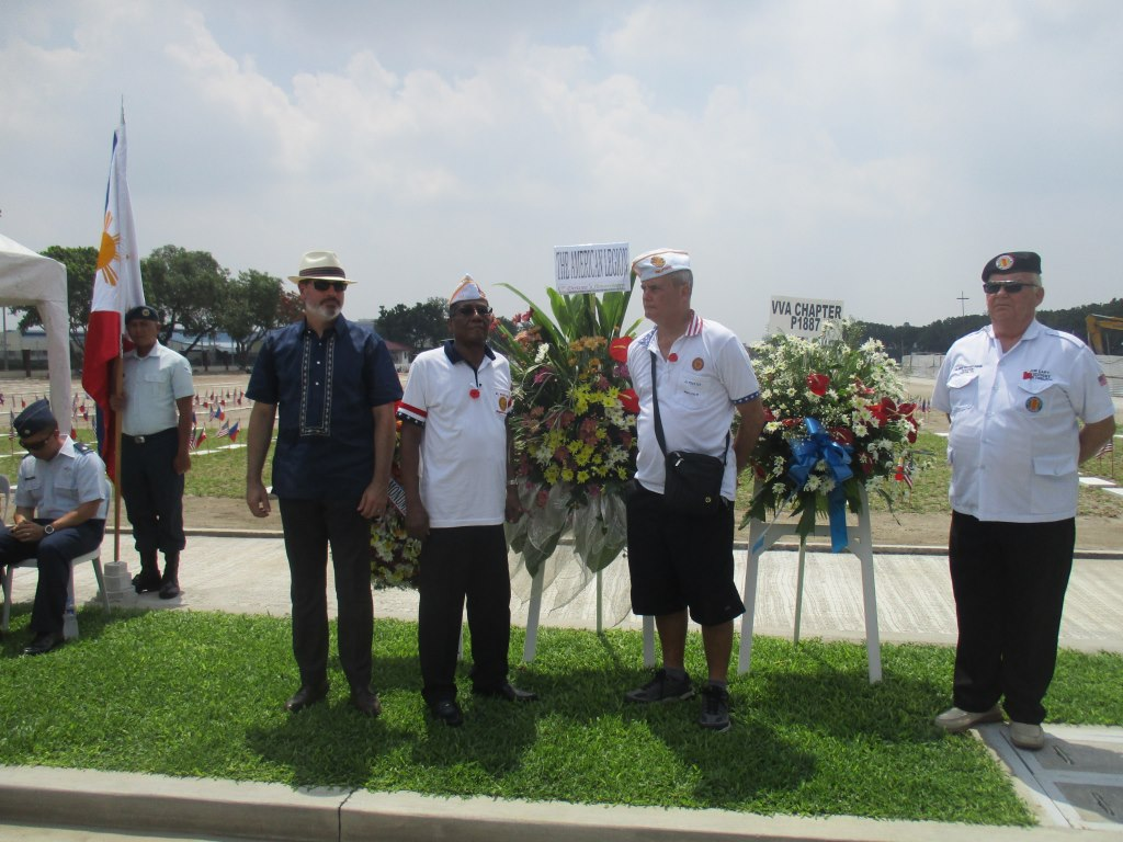 Men stand next to the stands holding the floral wreaths.