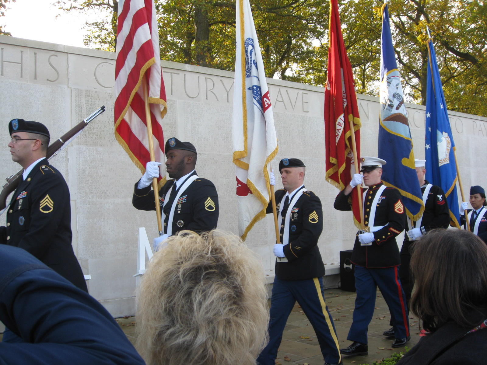 A Joint Honor Guard marches in front of the Walls of Missing during the ceremony.