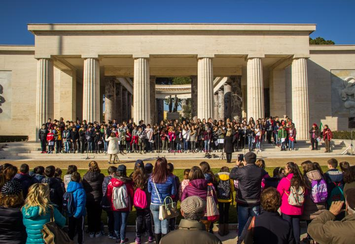 A large group of students stand on the steps of the memorial building to sing.