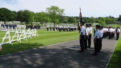 French and American military stand in formations during the ceremony.
