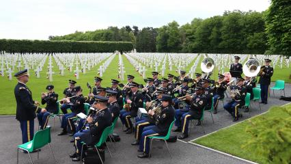 Men and women in uniform sit while they play their instruments.