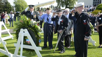 Men salute after laying a wreath.