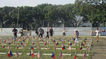 Volunteers place an American and Filipino flag at every grave site.