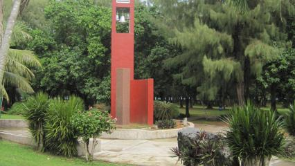 Amidst greenery, a memorial area includes a granite column.
