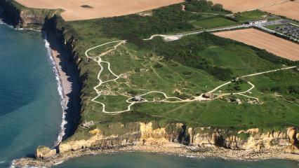 An aerial view of Pointe du Hoc shows the English Channel, the cliffs of the Pointe and the cratered ground.