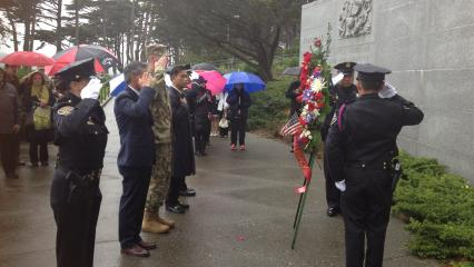 People salute after laying a wreath at the memorial.