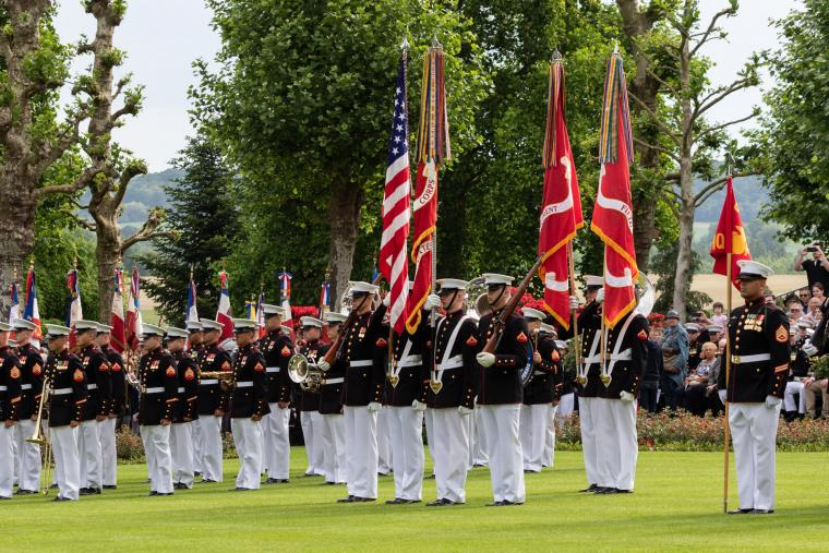 Marines in uniform stand and participate during the ceremony.
