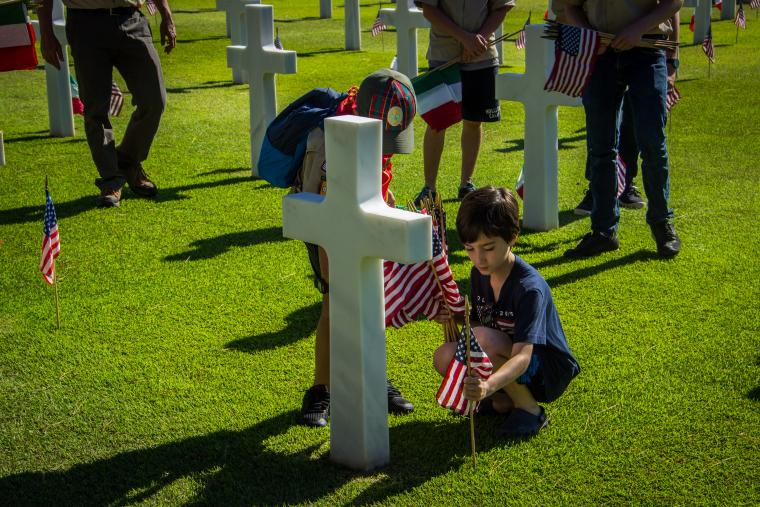 Boys kneel down to place the flags.