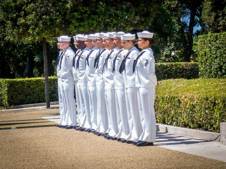 Men and women in uniform stand with their hands behind their back.