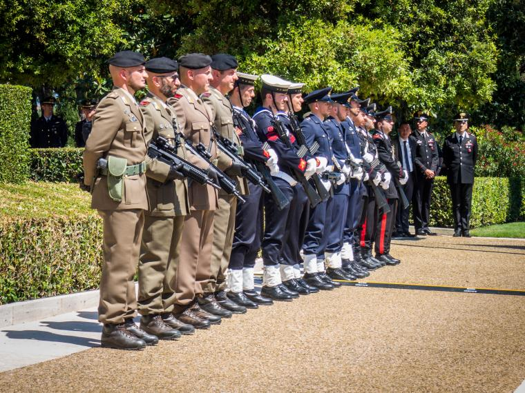 Men in uniform stand in a straight line.