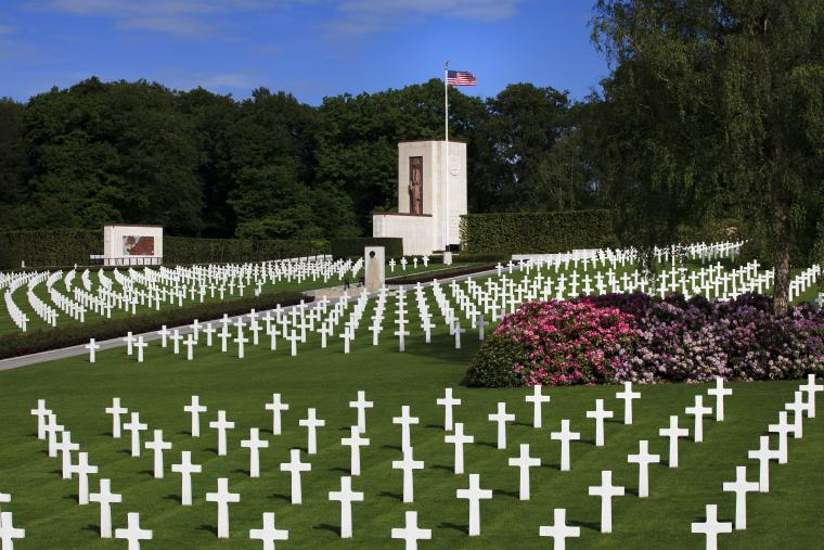 Rows of marble headstones are seen in front of the chapel at Luxembourg American Cemetery.