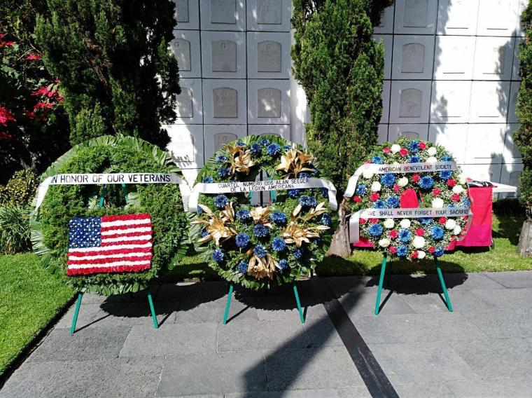 Three large floral wreaths on stands in front of the crypt.
