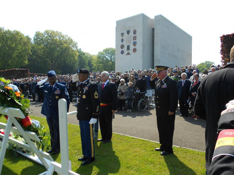 U.S. military stand saluting floral wreaths with large crowd in the background.
