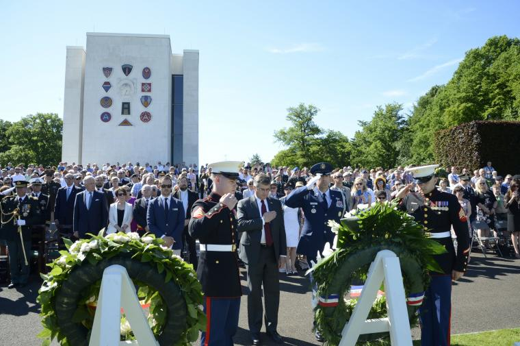 Men in uniform salute after the wreath is laid.
