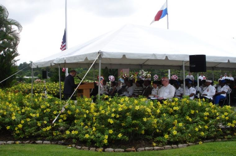 Attendees sit under tent with speaker at podium and floral bushes surround tent.