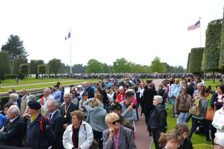 Crowds of people stand at Normandy Cemetery