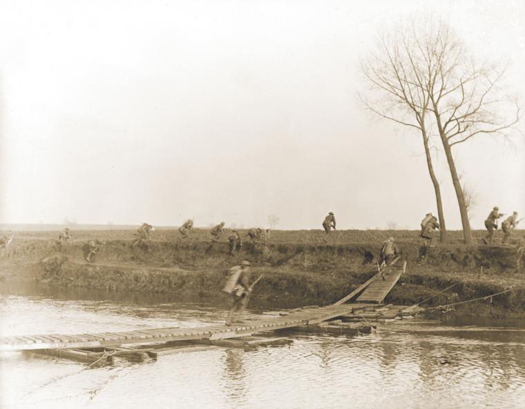 Soldiers of the 146th Infantry, 37th Division, crossing the Scheldt River at Nederzwalm under fire.