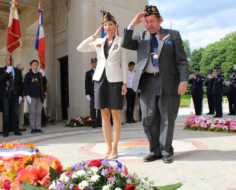 A man and woman salute after laying a wreath.