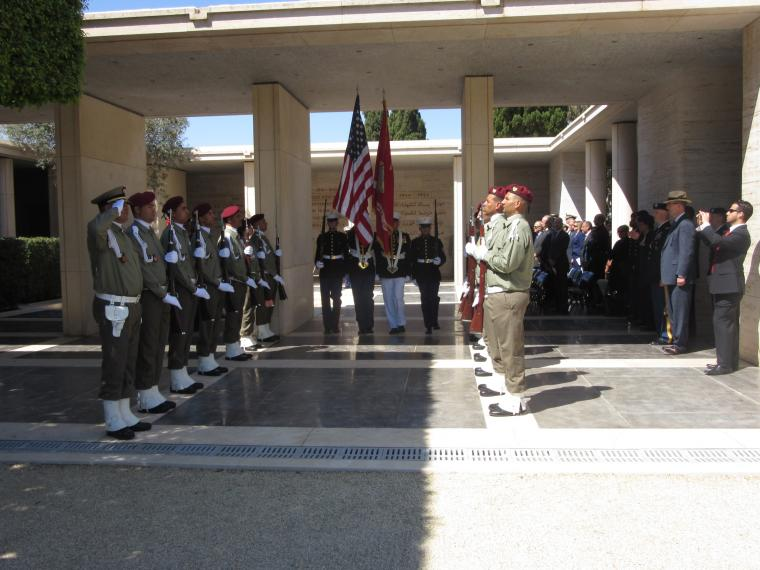 The Honor Guard departs while members of the Tunisian military stand in straight lines on both sides.