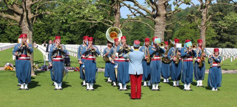 Members of the band in uniform play their instruments.