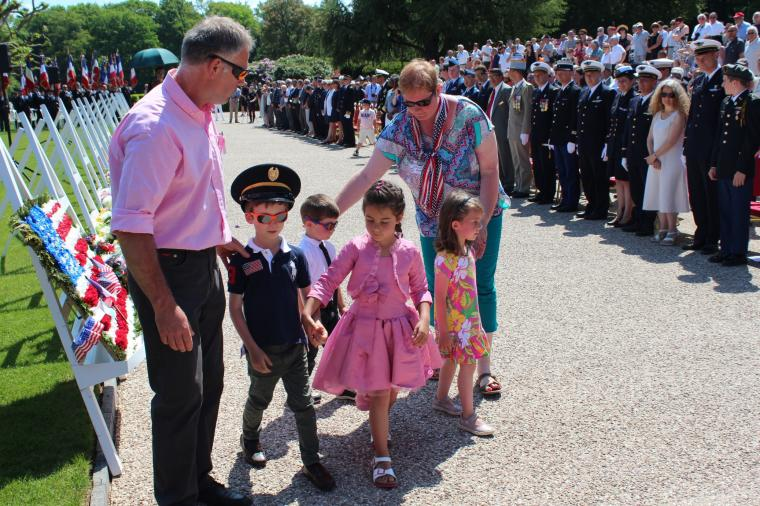 Young children walk away after having laid a floral wreath.