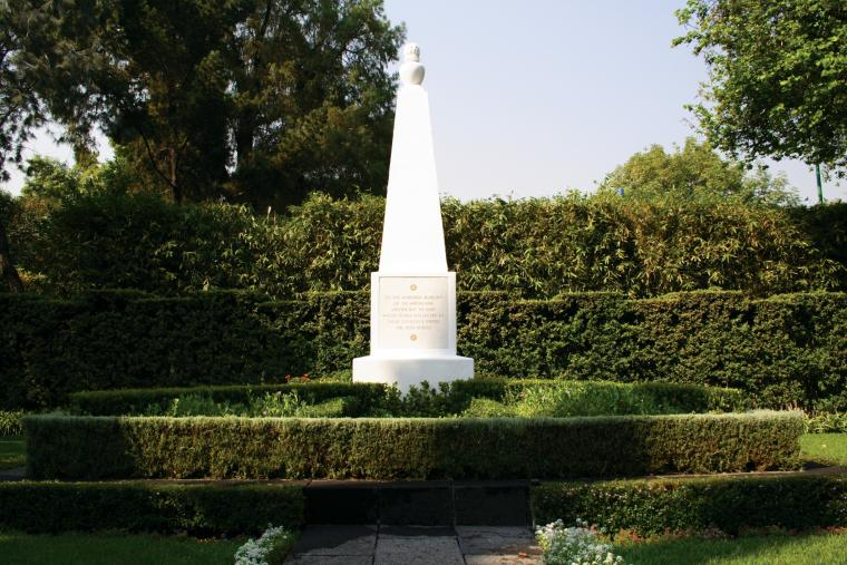 A small white monument at Mexico City National Cemetery sits among bushes.
