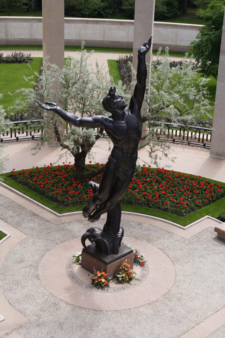 A bronze sculpture is at the center of the Normandy American Cemetery memorial area.