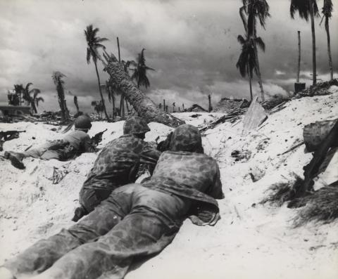Marines lay in the sand as they fire on pill boxes in the distance.
