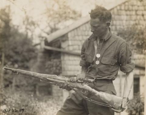 Historic photo shows man with rifle in hand.
