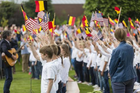 Children wave American and Belgian flags as they sing.