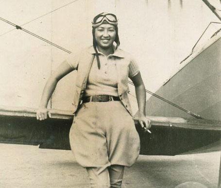 Lee, dressed in flying gear, leans against her plane.