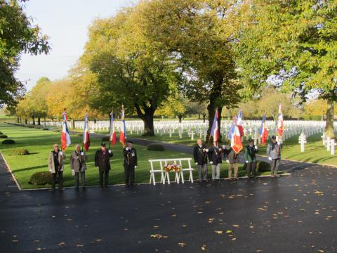 Men with flags flank the floral wreath that was laid on a stand.