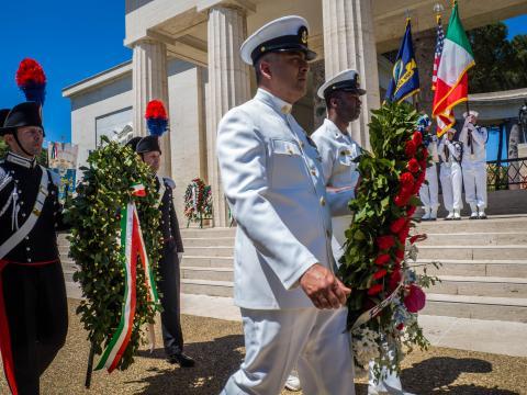 Men in uniform carry floral wreaths.