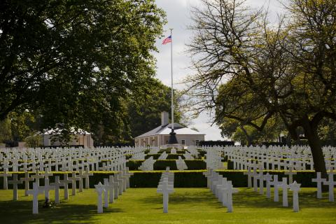 Rows of headstones are seen with an American flag flying high in the background.