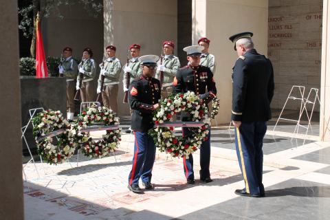 Two Marines present a floral wreath to a man in uniform.