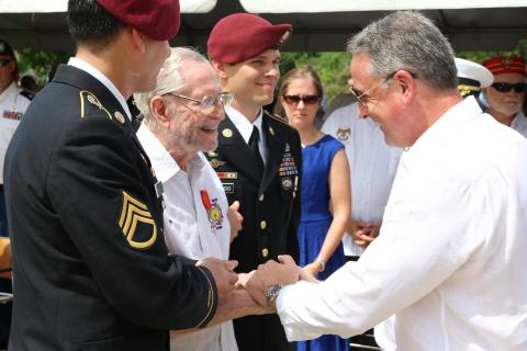 The U.S. Ambassador shakes hands with Herbert Friedlander, who is flanked by two American soldiers.