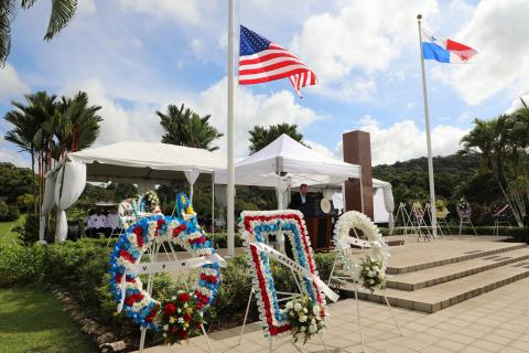 Floral wreaths sit on stands in front of the podium area.
