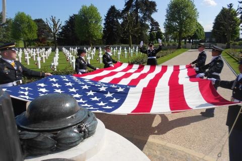 Members of the American military fold a large American flag.