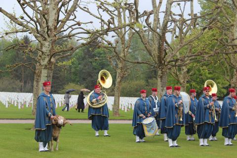 A French military band stands in front of the headstones.