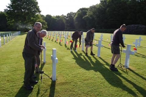 Men place American and Belgian flags in front of every headstone.