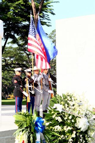 Men in uniform stand with flags.