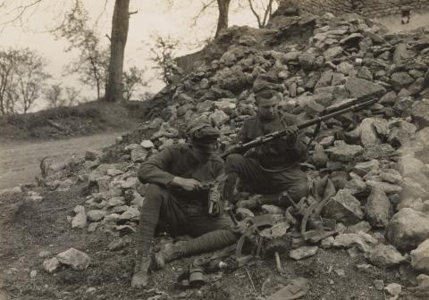 Historic photo shows soldiers sitting on rubble examining items.