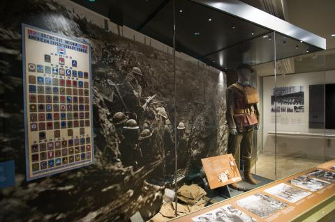 Exhibit shows large historic image of soldiers as well as a mannequin in uniform.