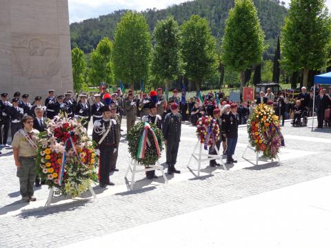 Large floral wreaths sit on stands next to the participants that laid the wreaths.