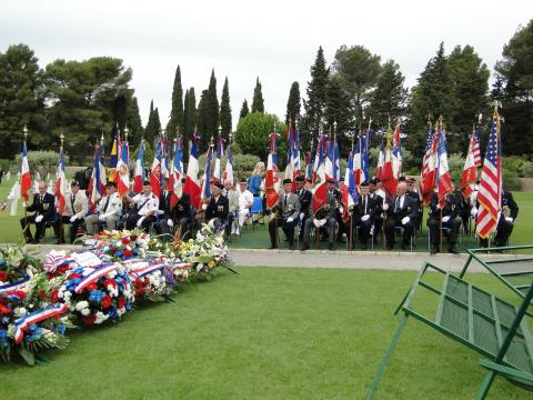 Flag bearers sit in chairs near the floral wreath stands.