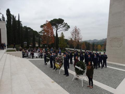 Members of the military along with two students stand next to floral wreaths.