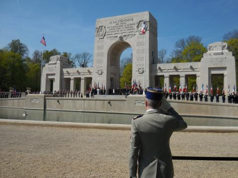 A member of the French military salutes as he faces the memorial.