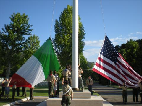Boy Scouts raise large Italian and American flags on a flag pole.