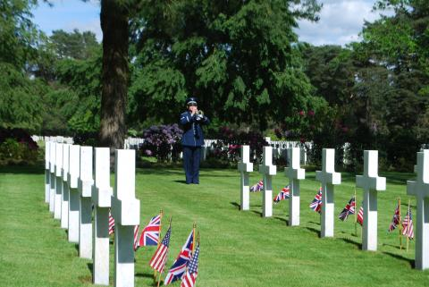 A bugler stands amongst the headstones and plays.