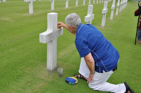 Touzel kneels on the ground as she takes a sponge to the headstone.